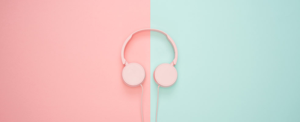 Over the ear headphones against a two tone pink & light torquoise pastel background