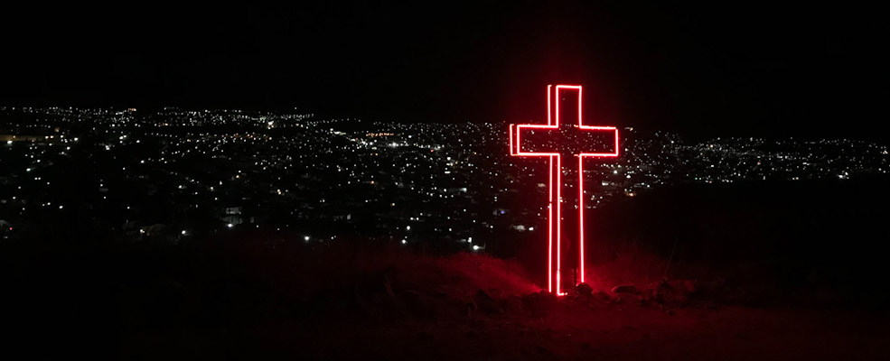 Neon cross glowing in the night